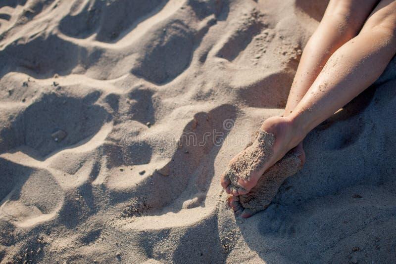 Die Füße des Mädchens auf Sand stockbild