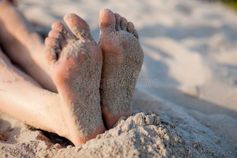 Die Füße des Mädchens auf Sand stockbilder