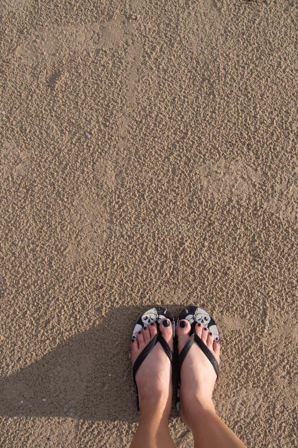 Die Füße des Mädchens Sandalen tragend, die auf dem Sand auf dem Strand standen lizenzfreies stockbild