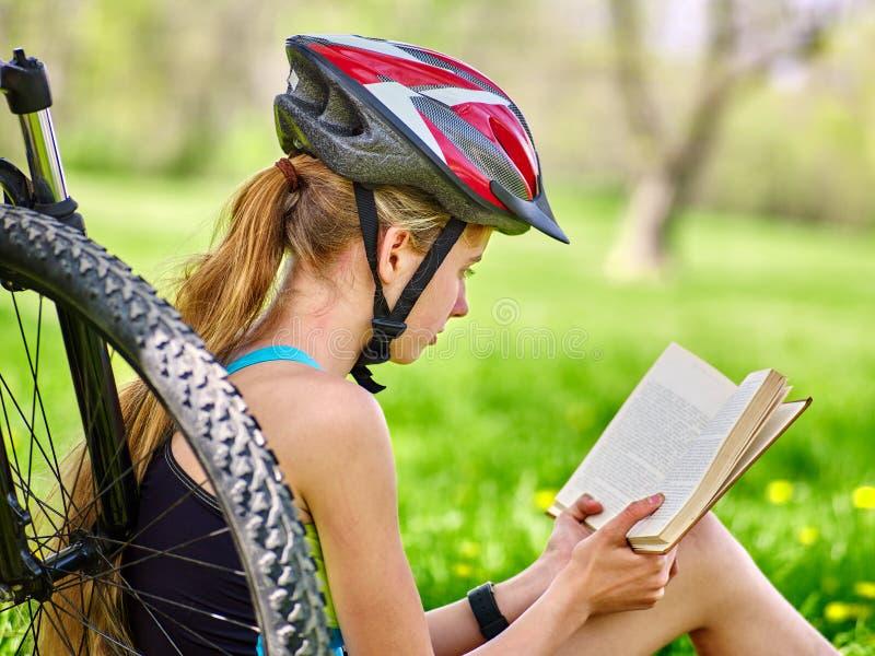 Die Fahrräder, die tragenden Sturzhelm des Mädchens radfahren, lasen Buchrest nahe Fahrrad stockbild