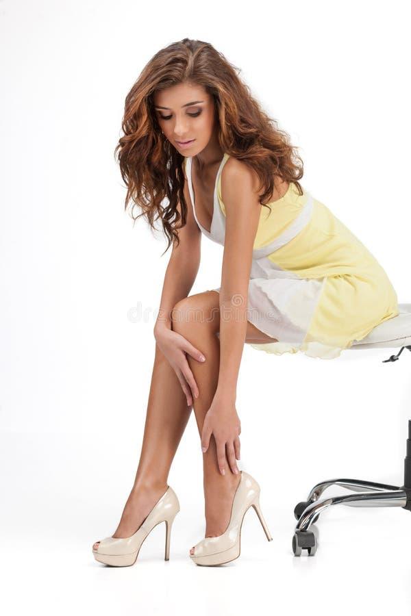 Die falsche Größe. Schöne junge Frauen, die auf dem Stuhl und dem t sitzen lizenzfreie stockfotografie