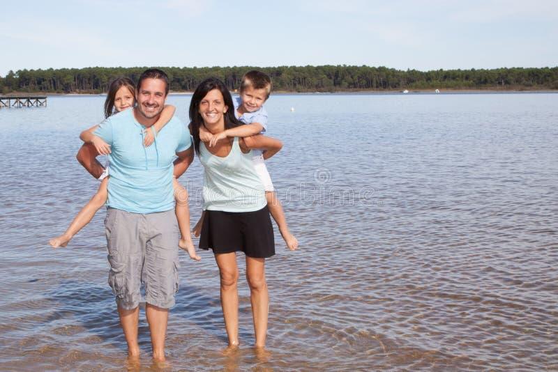 Die Familie, die entlang Sandy Beach-Eltern geht, haben die Kinder lizenzfreies stockfoto