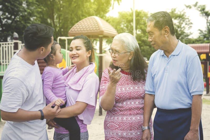 Die Familie mit drei Generationen trägt Sportkleidung im Park lizenzfreie stockfotografie