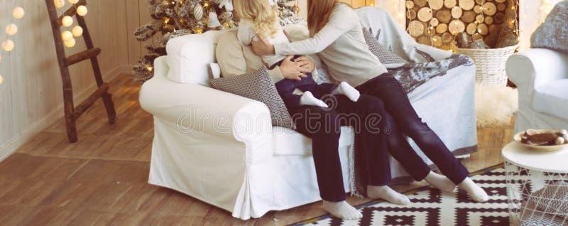 Die Familie nahe dem Kamin und dem Weihnachtsbaum sitzt auf der Couch, das Mädchen erreicht heraus zu ihrem Vater, umarmen ihn Co stockbilder