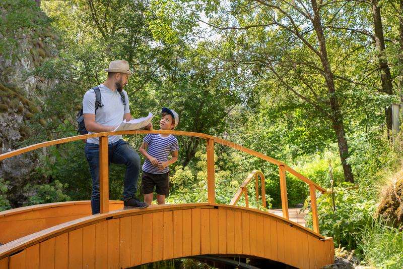 Die Familie reist Der Sohn und Vater der Hiker stehen auf der Brücke und schauen sich eine Karte an und reden stockfotografie