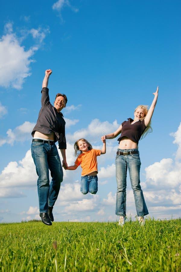 Die Familie springend auf Wiese am Sommer lizenzfreie stockbilder