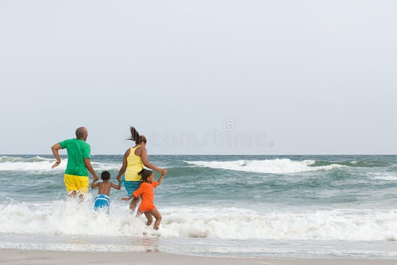 Die Familie springend in das Meer stockbild
