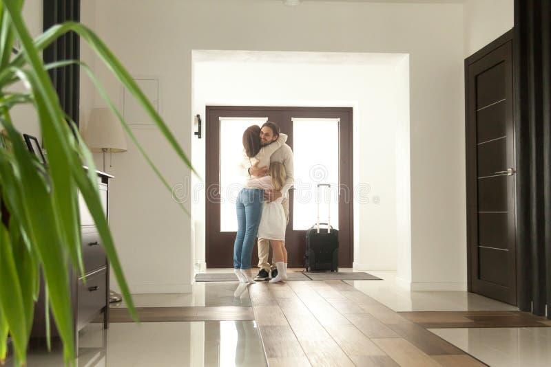 Die Familie, die Vater umarmt, kam kam nach Hause an, zurückgehend nach Geschäft lizenzfreie stockfotografie