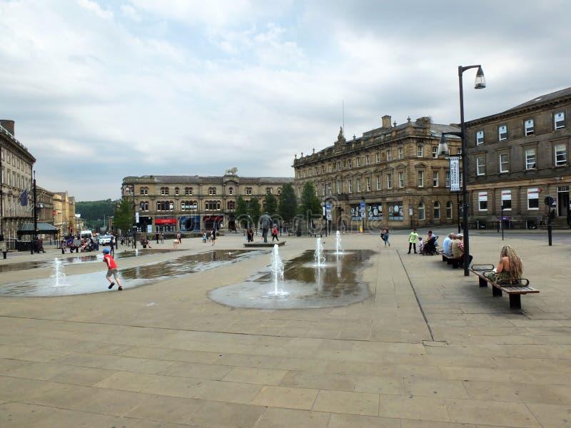 Die Familien und Kinder, die in den Brunnen im Fußgänger-St- George` s spielen, quadrieren in Huddersfield Yorkshire lizenzfreie stockfotografie