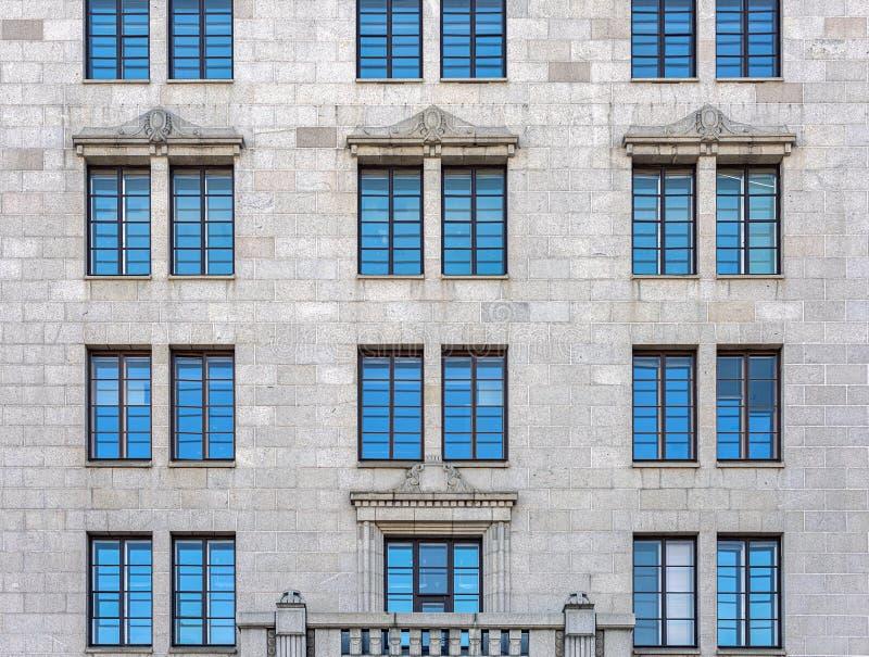 Die Fassade des Stadtgebäudes gegenübergestellt mit grauem Stein Die Fenster reflektieren den blauen Himmel lizenzfreie stockfotos