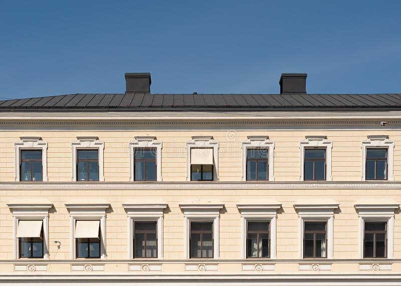 Die Fassade des Stadtgebäudes, -windows und -dachs gegen den blauen Himmel stockfoto