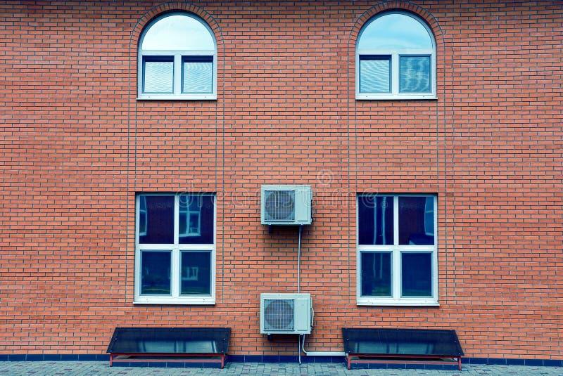 Die Fassade eines Backsteinbaus mit Fenstern und Klimaanlage lizenzfreie stockbilder