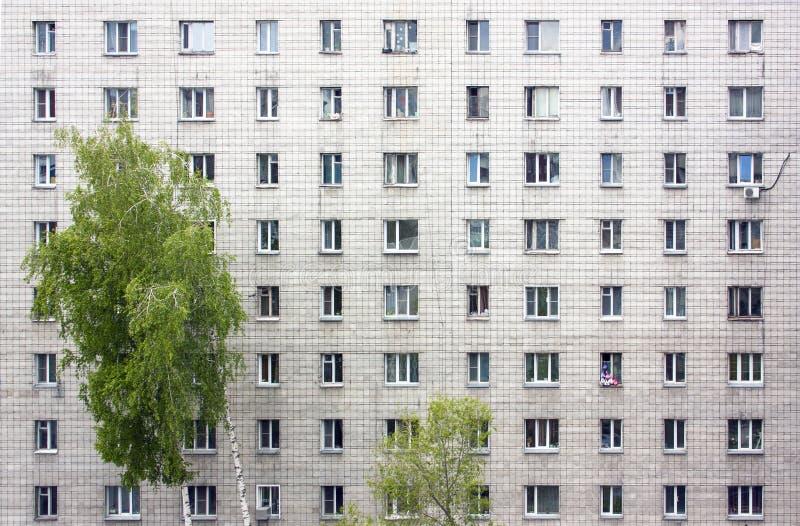 Die Fassade eines mehrst?ckigen Wohngeb?udes Viele Fenster stockfotografie