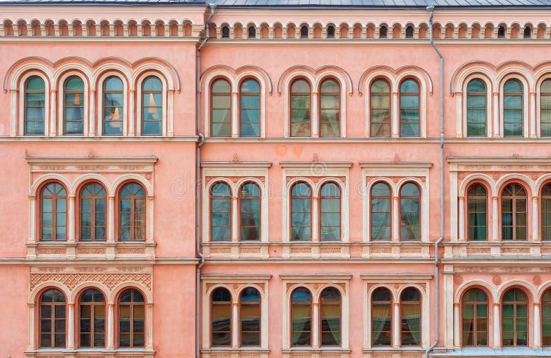 Die Fassade eines schönen rosa Stadtgebäudes Windows mit halbkreisförmigem Teil stockbild