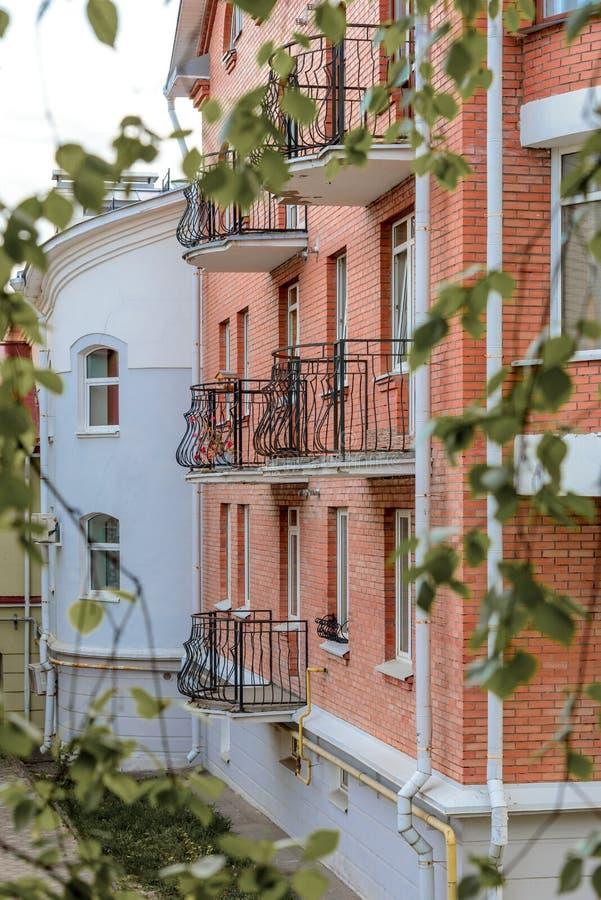 Die Fassade von Backsteinhäusern mit Schmiedeeisenbalkonen auf Hintergrund von grünen Blättern stockfotografie