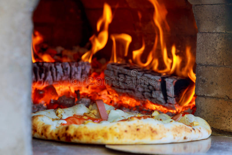 Die feinschmeckerische Pizza, die heraus Holz kommt, feuerte Pizza-Ofen im Restaurant ab stockbild