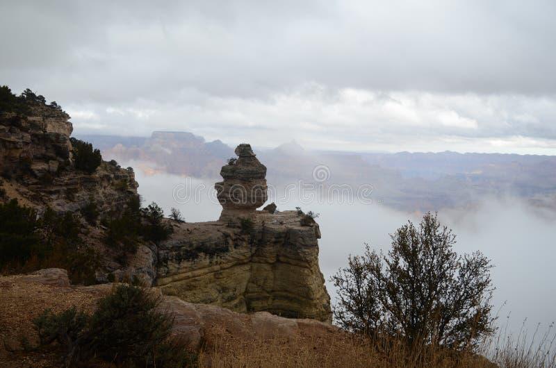 Die Felsformation in Grand Canyon sieht wie eine Person in der schweren Kleidung aus, die auf einem Steinstuhl sitzt, der eine To lizenzfreies stockbild