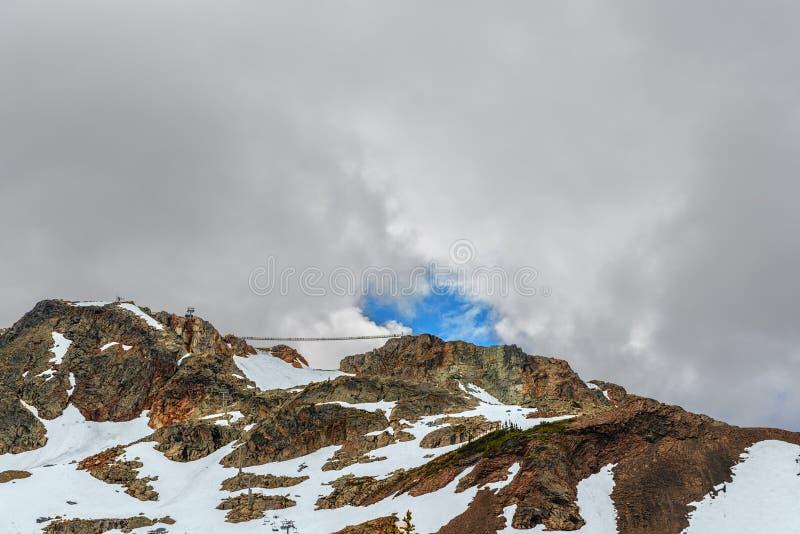 Die felsigen Berge, die mit Schnee bedeckt werden, treibt, eine Drahtseilbahn mit gondo lizenzfreies stockbild