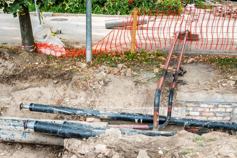Die Fernheizungsrohrleitungswiedergutmachung und -rekonstruktion, die zur Straße mit orange Baustelle-Sicherheitsnetz parallel si lizenzfreie stockfotografie
