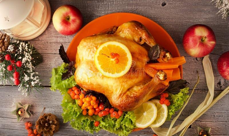 Die festliche gebratene Türkei auf Servierplatte mit Beeren, Salat, Äpfeln und Kerzen auf hölzernem Hintergrund, stockfoto