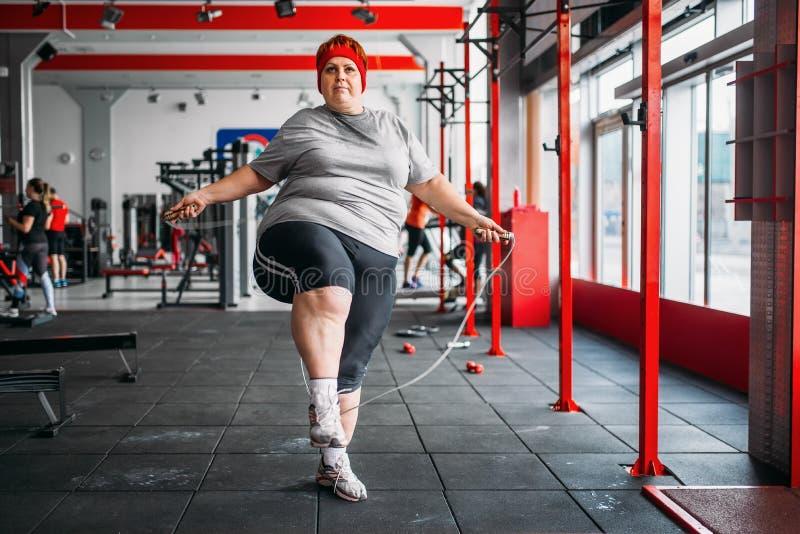 Die fette verschwitzte Frau, die Übung mit tut, fangen Turnhalle ein lizenzfreies stockbild