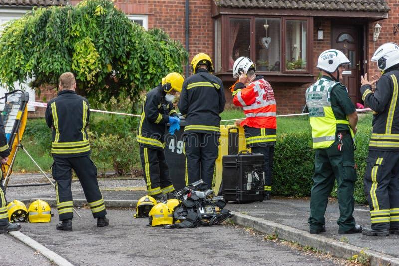 Die Feuerwehrmänner, die angekleidet erhalten, beim Sicherheitsgangvorbereiten kommen nach Hause mit vermutlich defektem chemisch lizenzfreies stockbild