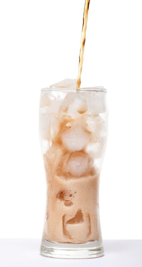 Die Flüssigkeit wird in ein Glas mit dem Eis gegossen, das auf einem weißen b lokalisiert wird stockbild