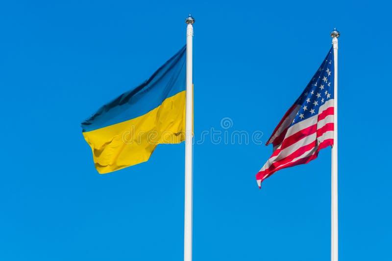 Die Flagge von Ukraine und die Flagge der Vereinigten Staaten von Amerika sind Einfluss im Wind neben einander auf Fahnenmasten stockbilder