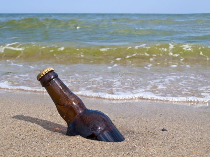 Die Flasche des Bieres wird im Sand begraben lizenzfreie stockbilder
