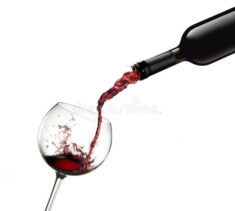 Die Flasche, die Rotwein im Glas mit gießt, spritzt lizenzfreie stockfotos