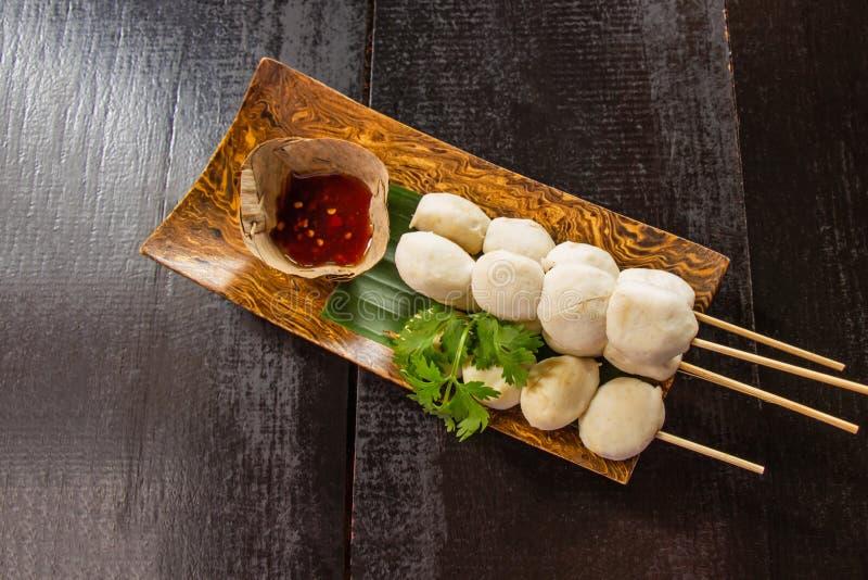 Die Fleischklöschen, die auf hölzernem Teller und einer Schale Soße verziert mit Koriander geröstet wurden, setzten auf dem Tisch lizenzfreie stockbilder