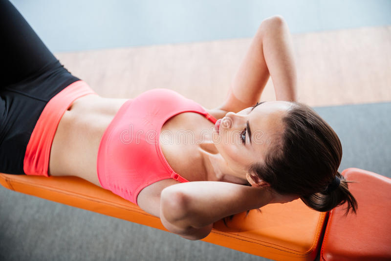 Die fokussierte Sportlerin, die ABS tut, knirscht auf Bank in der Turnhalle stockbilder