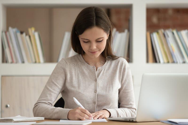 Die fokussierte Studentin machen Anmerkungen studierend am Laptop lizenzfreies stockfoto