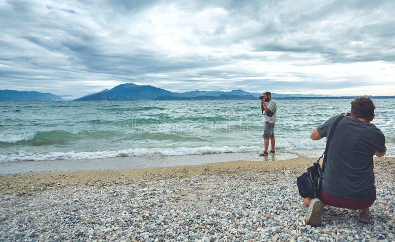 Die Fotografen, die auf dem Meer schießen, setzen am bewölkten Tag auf den Strand lizenzfreies stockbild