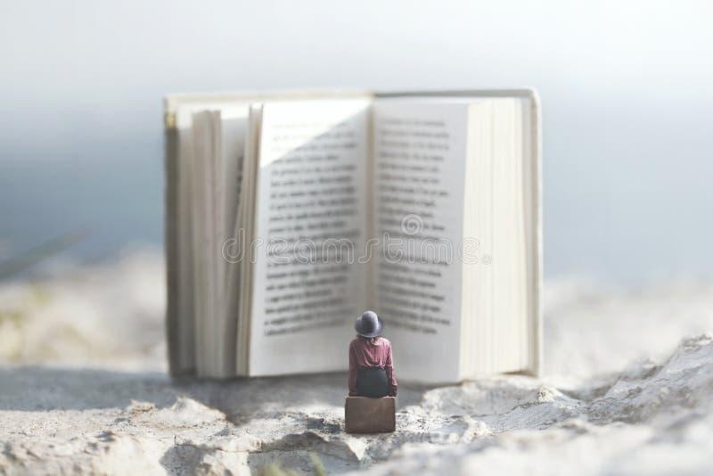 Die Frau, die auf einem Koffer sitzt, liest ein riesiges Buch stockfoto