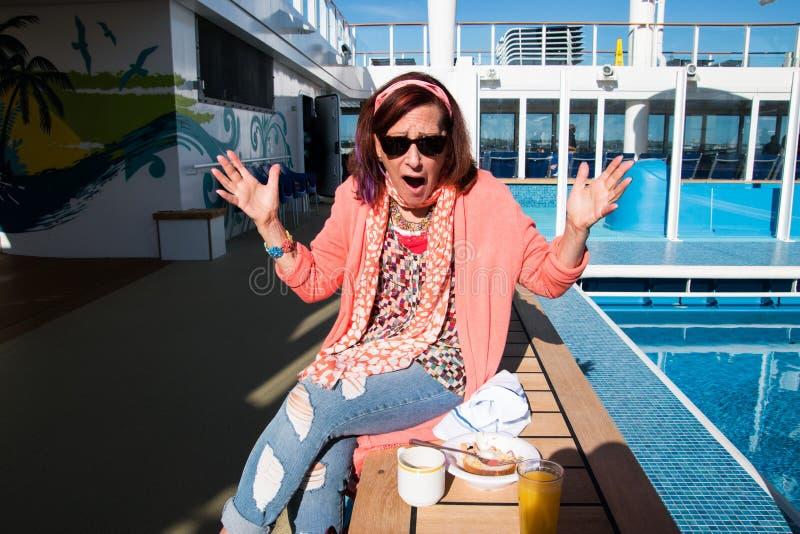 Die Frau auf Kreuzschiff Frühstück auf einer Bank essend störte, dass es keine Tabellen gab, die am Buffet gelassen wurden stockfotografie