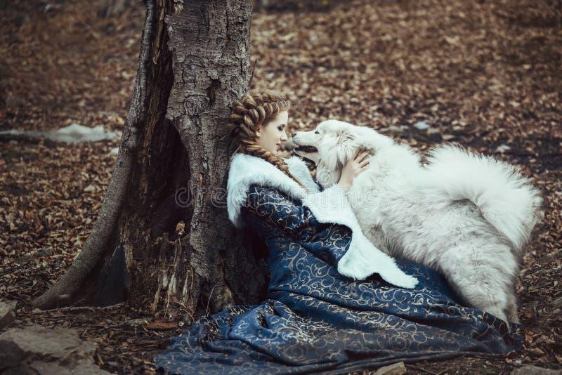 Die Frau auf Winterweg mit einem Hund lizenzfreies stockfoto