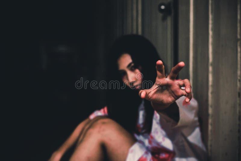 Die Frau, die aus den Grund in verlassenem Haushalloween-Konzept sitzt lizenzfreies stockfoto
