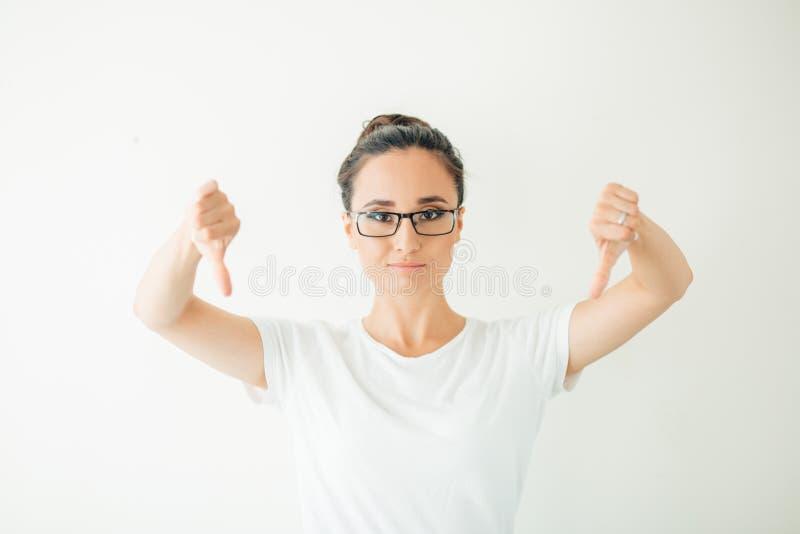 Die Frau, die Daumen gestikulieren gibt unten, das Schauen mit negativem Ausdruck und Missbilligung stockfoto