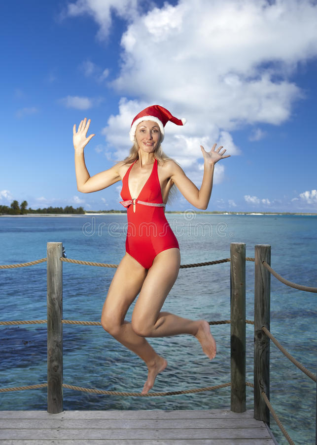 Die Frau in der Sankt-Klaus-Kappe des neuen Jahres auf Hintergrund von Meer springt stockfotografie