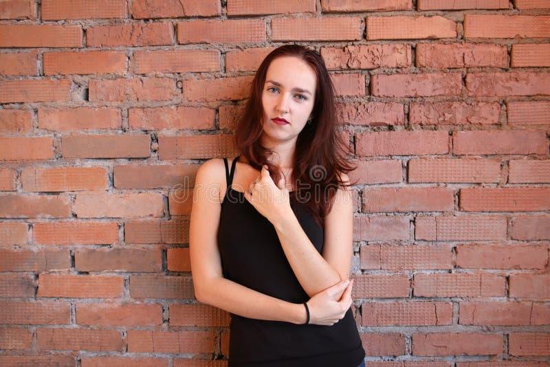 Die Frau in der schwarzen Spitze wirft nahe einer Backsteinmauer auf lizenzfreie stockfotos