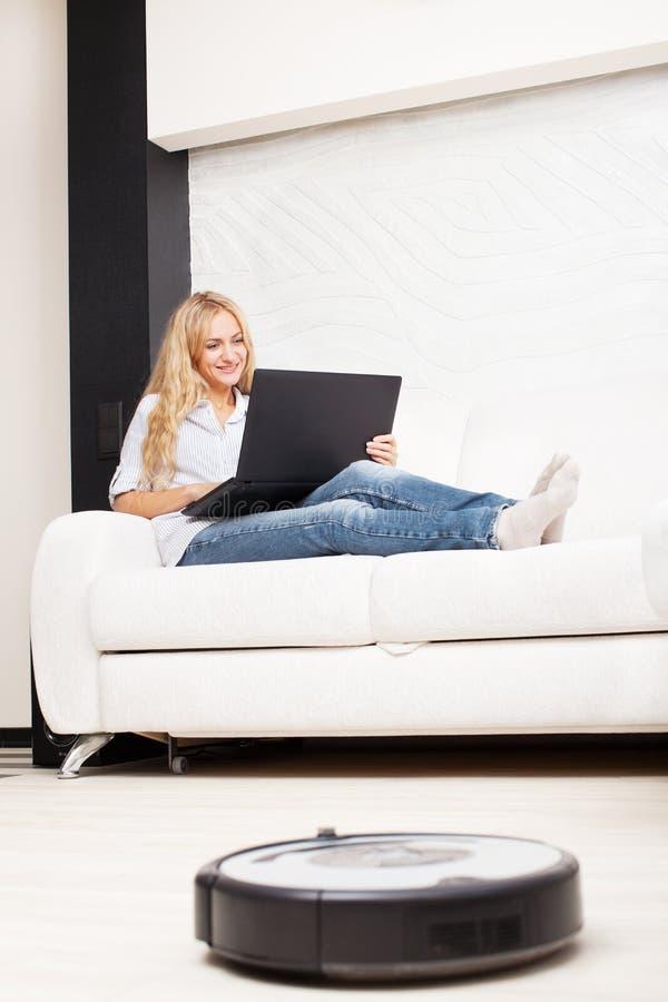 Die Frau, die auf dem Sofa liegen, und der RoboterStaubsauger säubert lizenzfreie stockfotografie