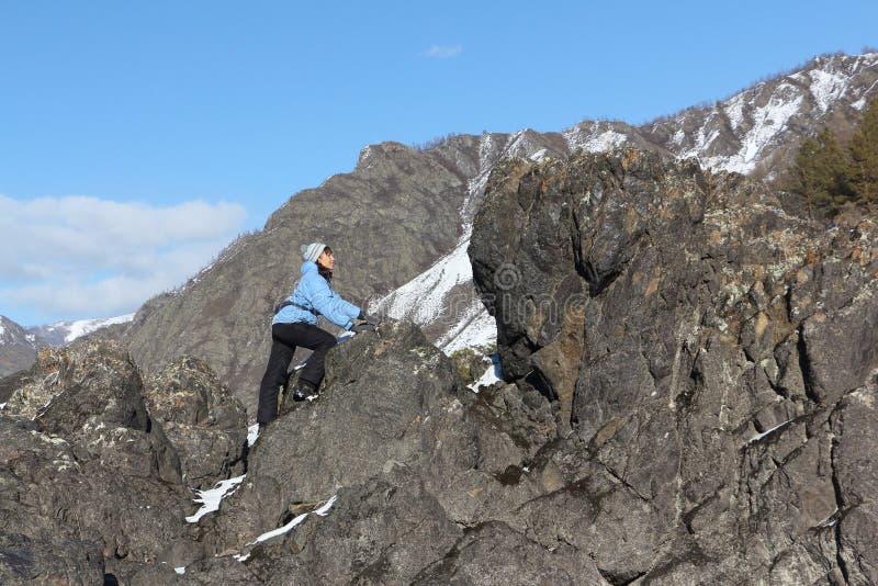 Die Frau, die den Felsen zur Gebirgsspitze klettert stockfotos