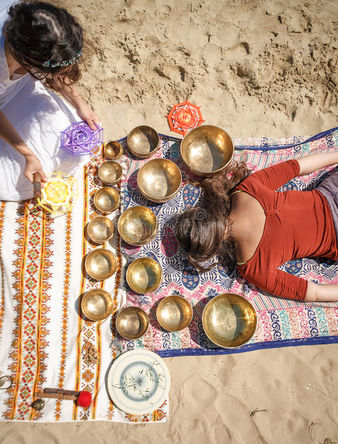 Die Frau, die einen Gesang spielt, rollt alias Tibetaner-Gesang-Schüsseln, Himalajaschüsseln Herstellung der soliden Massage stockfotos