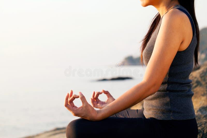 Die Frau, die in einer Yogahaltung meditiert lizenzfreie stockfotos