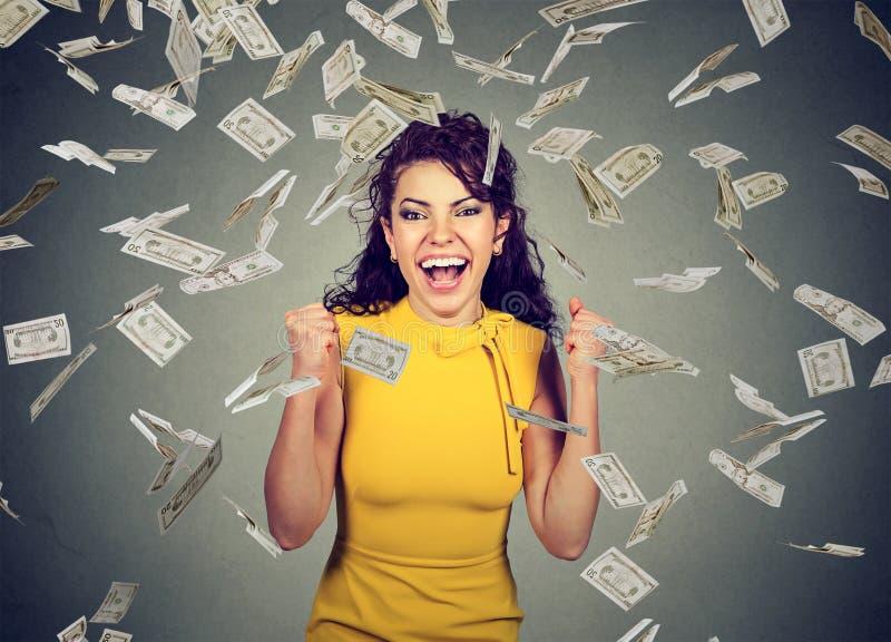 Die Frau, die Fäuste pumpt, feiert Erfolg unter Geldregen lizenzfreies stockbild