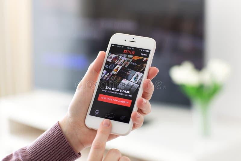 Die Frau, die iPhone mit APP Netflix hält, stellt das Strömen von Medien zur Verfügung stockbilder