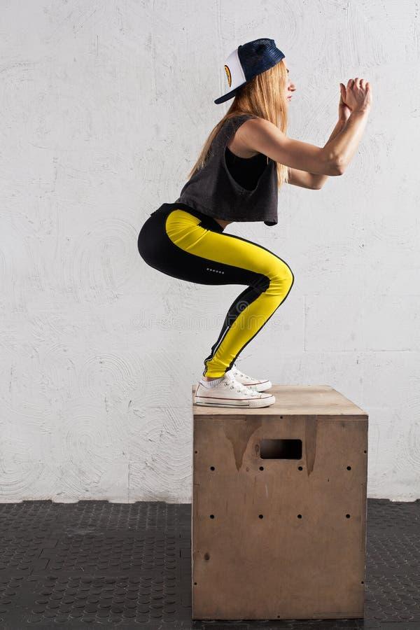 Die Frau, die Kasten tut, springt in die Turnhalle lizenzfreies stockbild