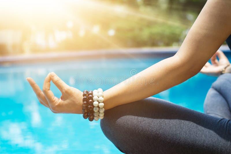 Die Frau, die mit dem Handgelenk meditiert, bördelt in einer Lotosyogaposition an Querstation stockbilder