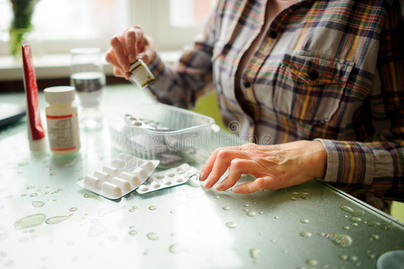 Die Frau, die rheumatoide Arthritis hat, nimmt Medizin ein stockbild